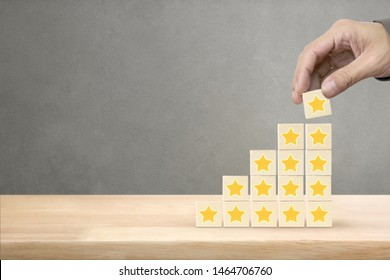 Hand arranging wood block stacking with icon star symbol, Rating customer service satisfaction experience concept.