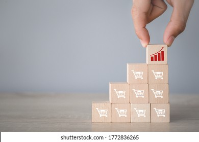 Hand arranging wood block stacking with icon Graph and shopping cart symbol upward direction,