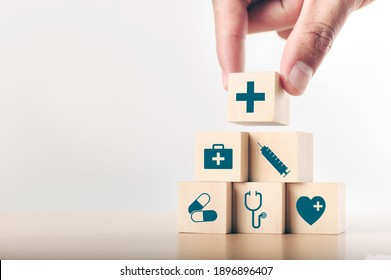 Hand arranging wood block stacking with the healthcare medical icon. Health insurance - health concept