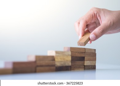 Hand arranging wood block stacking as step stair. Business concept for growth success process.
