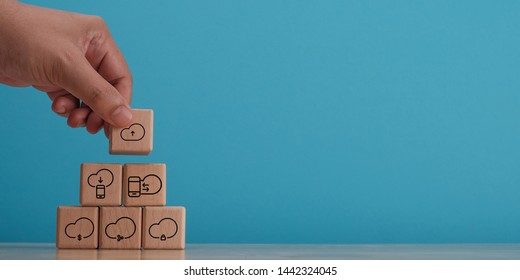 Hand arranging wooden block with symbol of cloud service, technology banner