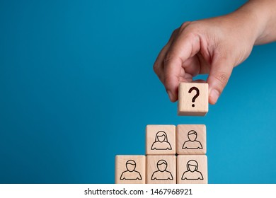 Hand arranging wooden block with symbol, people symbol with question mark on top, leadership election recruitment concept