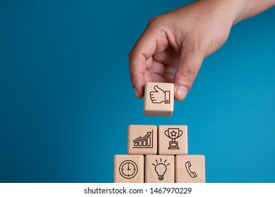 Hand arranging wooden block with symbol, customer service concept