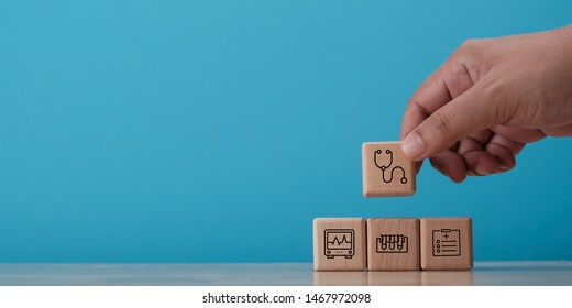 Hand arranging wooden block with symbol, medical concept