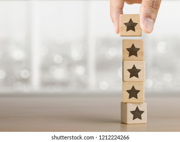 Hand arranging wooden blocks with the five star symbol. The best rating, the best ranking, the best service, goal, success concept.