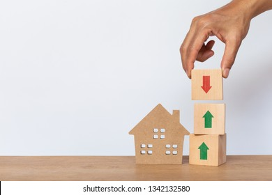 Hand arranging wooden cube stack with arrow pointing up and arrows down, house model on white background. Home taxes decrease concept