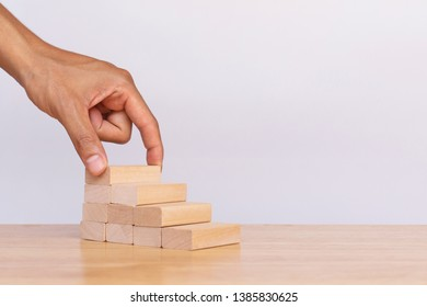 Hand arranging wooden cube stack a staircase on white background. Concept of success, winner, victory or top ranking