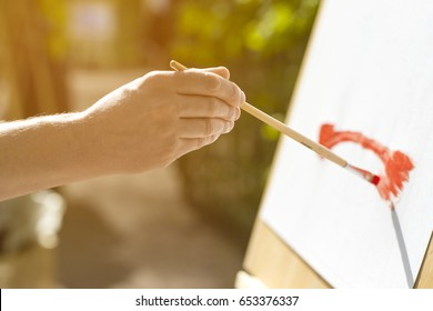 Hand of an artist beginning to paint a picture of a bridge