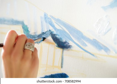 hand of artist with brush painting on canvas, close-up