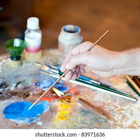 Hand of the artist with a paintbrush and Artistic equipment: paint, brushes, spatula and art palette