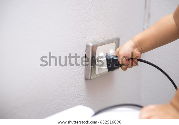 Hand of an Asian  baby trying to insert plug into electrical outlet covered with safety plugs