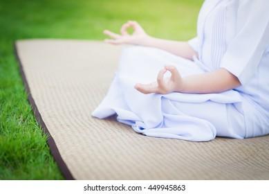 Hand of Asian girl wearing white dress meditating in lotus position