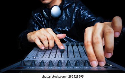 hand of asian handsome DJ, producer working on digital studio mixer for night club, radio, TV broadcasting background