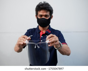 hand asian man holding face shield for healthcare with outdoor.