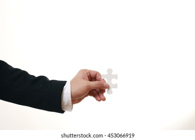 Hand of the Asian man holding puzzle.