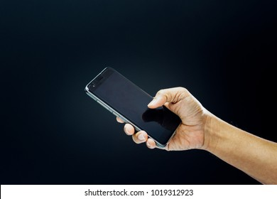 Hand of asian man holding smartphone in technology and communication concept on black background dark style