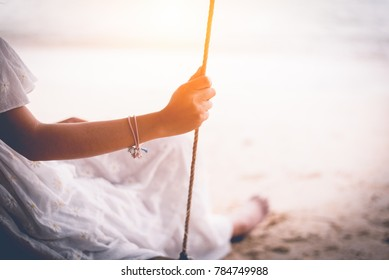 Hand of Asian woman on white dress sitting on swing at beach. People and Nature concept. Sad love and Missing someone concept. Lonely and Heart broken theme. Close up hand