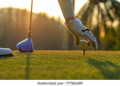 Hand asian woman putting golf ball on tee with club in golf course outdoors on evening and sunset time for healthy sport.  Lifestyle Concept