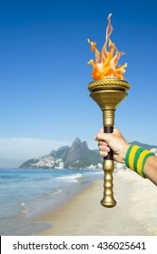 Hand of an athlete wearing Brazil colors sweatband holding sport torch on Ipanema Beach with Two Brothers Mountain on the skyline of Rio de Janeiro, Brazil