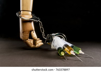 Hand attached to syringes with handcuffs. Metaphor of drug addiction. Isolated on dark background. With copy space text. Studio Shot.