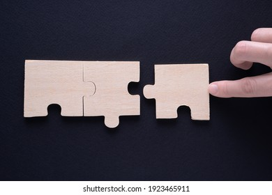 Hand attaches the missing piece of the puzzle. Business concept with wooden jigsaw puzzle on black background. Incomplete wooden puzzles, top view, flat lay. The concept of logical thinking.
