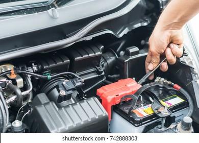 Hand of auto mechanic repair car battery in car repair shop