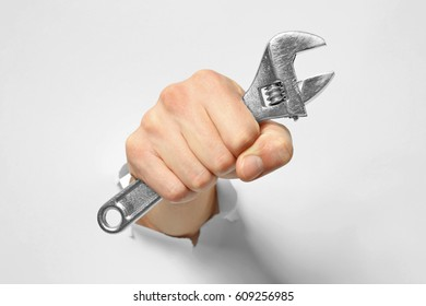 Hand of auto mechanic with wrench tearing white paper background