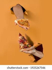 Hand vom Hintergrund hält eine Scheibe Pizza. Tortenhintergrund-Konzept