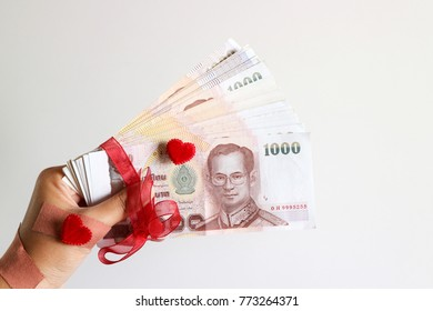 Hand with bandages hold pile of Thai Baht money with red ribbons and red hearts in white background