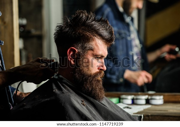 Hand of barber with hair clipper, close up. Hipster bearded client getting hairstyle. Barbershop concept. Man with beard in hairdressers chair, salon background. Barber works with hair clipper.