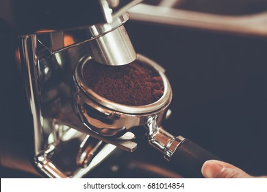 Hand of Barista put a portafilter to espresso machine for brewing coffee,color vintage style ,Thailand