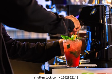 hand bartender make cocktail. Cocktail have cherry and mint leaves.