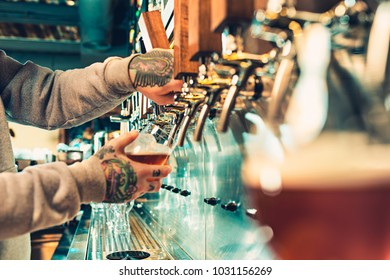 Hand of bartender pouring a large lager beer in tap. Soft, vintage instagram effect on photo. Pouring beer for client. Side view of young bartender pouring beer while standing at the bar counter
