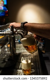 Hand of bartender pouring a large lager beer in tap. Rest in a bar with friends
