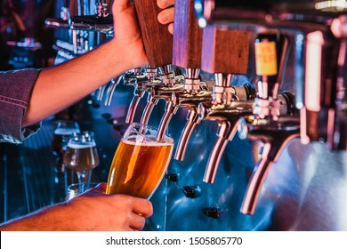Hand of bartender pouring a large lager beer in tap. Bright and modern neon light, males hands. Pouring beer for client. Side view of young bartender pouring beer while standing at the bar counter. - Shutterstock ID 1505805770