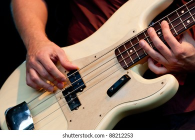 Hand of bass player while playing bass, colorful background