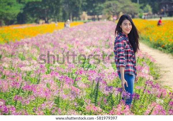 Hand Beautiful girls touching flower with at a sunset in meadow grass.
