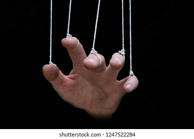 A hand being controlled by strings