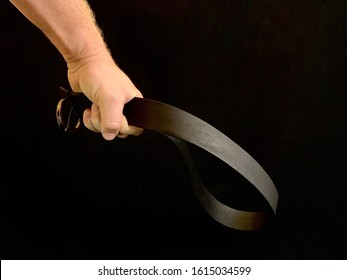 In a man's hand, a belt for punishment, on a black background. A man holds a belt in his fist. The father is going to punish the child with a belt. Concept: punishment, parenting, domestic violence