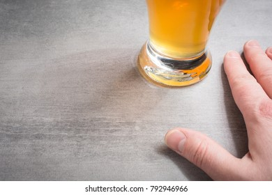 Hand beside a glass of beer on a stone background.