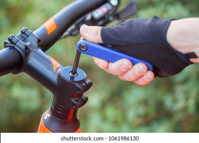A hand in a bicycle glove with a multitool twists the mount on the handlebar.