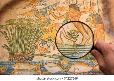 hand with big magnifying glass on old antique egyptian papyrus discovering