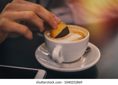 hand with biscuit in the cup of coffee, breakfast and snack