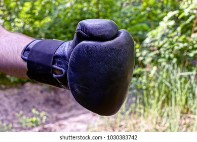 A hand in a black boxing glove on the street