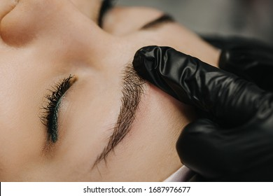 A hand in a black glove, with an index finger, draws eyebrows along the hairs, spreading it from side to side to demonstrate the finished work of microblading in close-up.