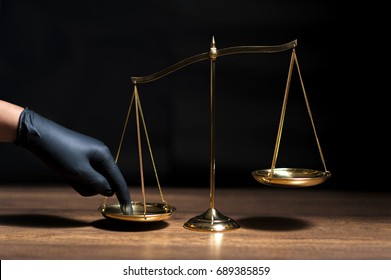 Hand with black glove pushing on scale of justice in dark room with black background. Concept of injustice, espionage, partiality, law.