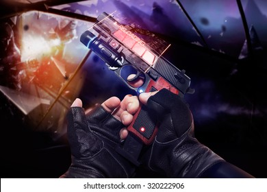 Hand in black gloves holding a red neon recharging handgun. First person view hand in black leather gloves holding a futuristic fantasy neon recharging handgun with clip and neon red, blue indicators.