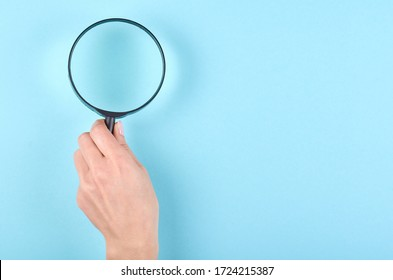 Hand with black magnifying glass on blue background. Flat lay, overhead view image. Copy space, template.