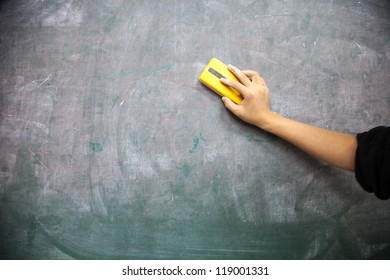 hand with blackboard eraser cleaning blackboard