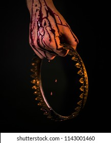 A hand in blood holds a golden crown with knitting needles, on which blood flows. Detailed and closeup photography.